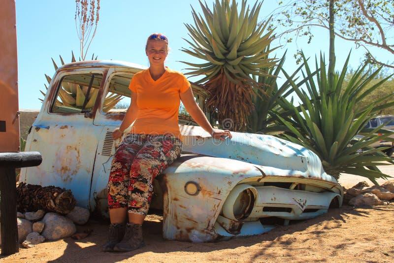 Övergav gamla rostiga bilar i öknen av Namibia och en fyllig vit turist- flicka nära den Namib-Naukluft nationalparken royaltyfria bilder