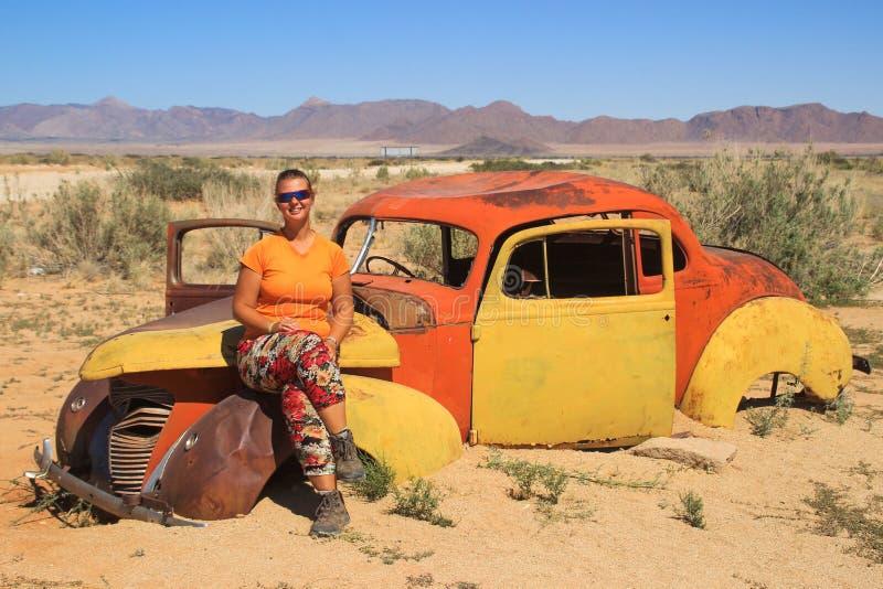 Övergav gamla rostiga bilar i öknen av Namibia och en fyllig vit turist- flicka nära den Namib-Naukluft nationalparken arkivbild