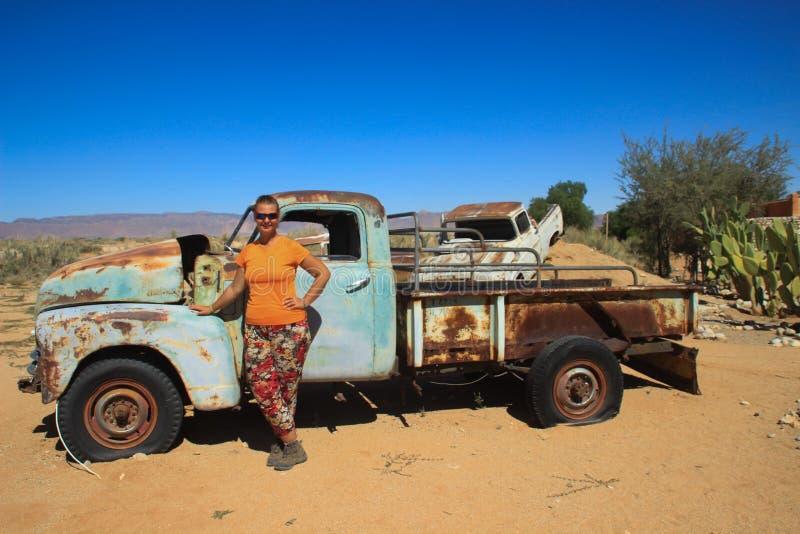 Övergav gamla rostiga bilar i öknen av Namibia och en fyllig vit turist- flicka nära den Namib-Naukluft nationalparken royaltyfria foton
