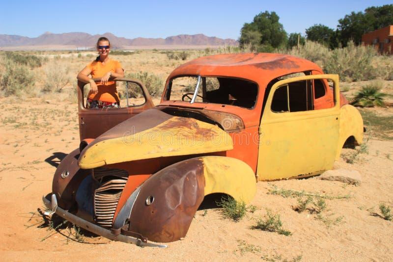 Övergav gamla rostiga bilar i öknen av Namibia och en fyllig vit turist- flicka nära den Namib-Naukluft nationalparken fotografering för bildbyråer