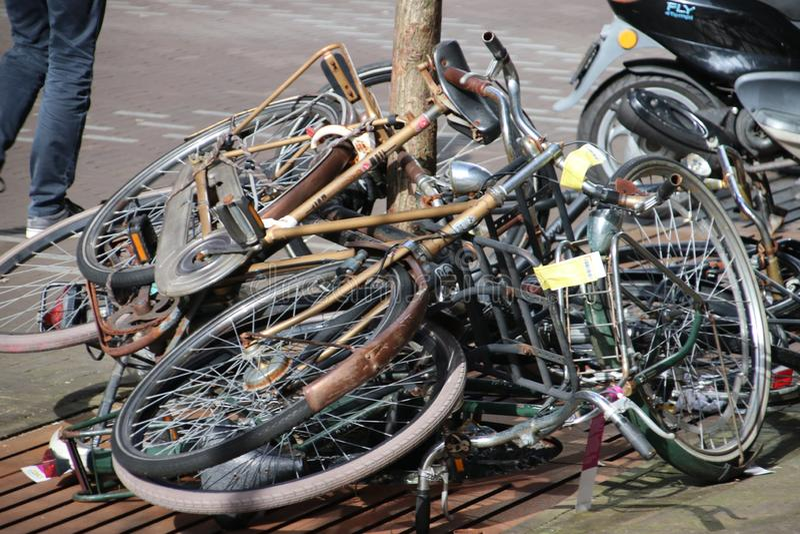 Övergav och gamla cyklar på gatan som markeras med etiketten som ska tas bort av kommunen av Den Haag i Nederländerna royaltyfria foton