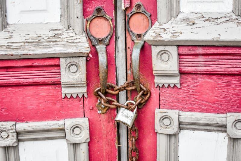 Övergav röda kyrkliga dörrar med kedjan och låset royaltyfri fotografi