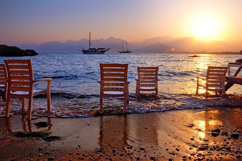 Övergav stolar på en sandig strand efter sommarsemester, medan två fartyg kryssar omkring along för en guld- solnedgång arkivbilder