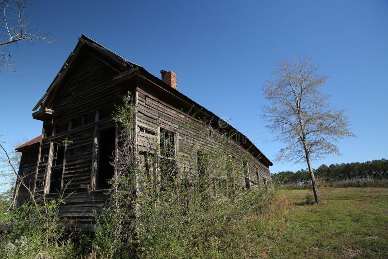 Övergett Alabama träskolahus nära röda jämna Alabama arkivfoto