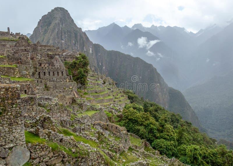 Övergett fördärvar av Machu Picchu den Incan citadellen, labyrinten av terrasser och väggar som stiger ut ur den tjocka undervege arkivbild