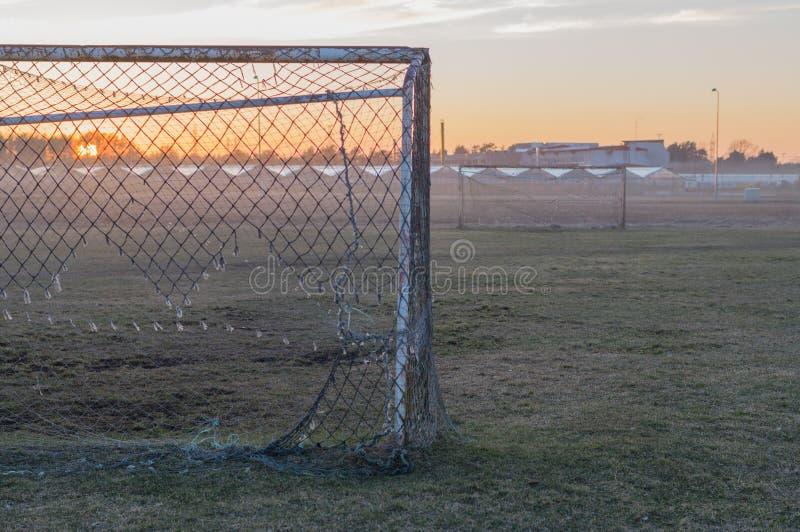 Övergett fotbollfält och gamla rostiga mål på solnedgång royaltyfria bilder