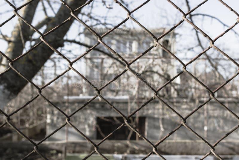 Övergett hus bak ett järnraster arkivfoto
