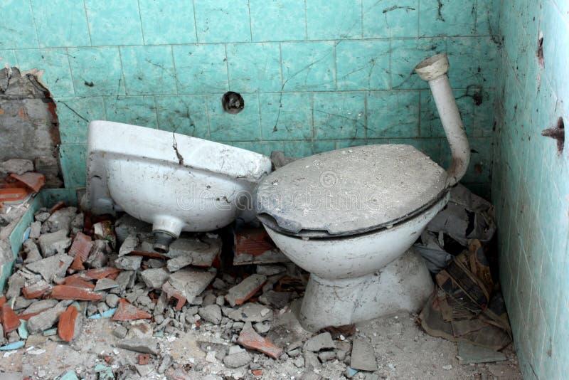 Övergett husbadrum med den brutna toaletten, vasken och tegelplattor royaltyfri bild