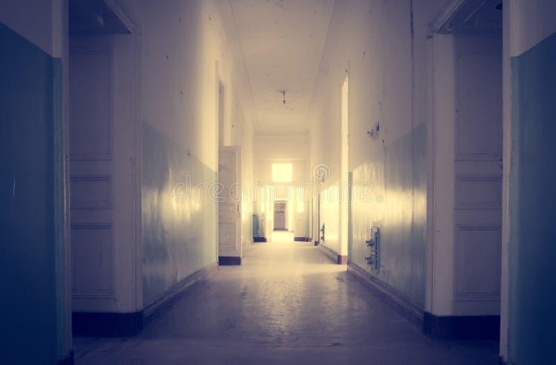 Övergett långt korridor och rum i gammalt hus arkivbild