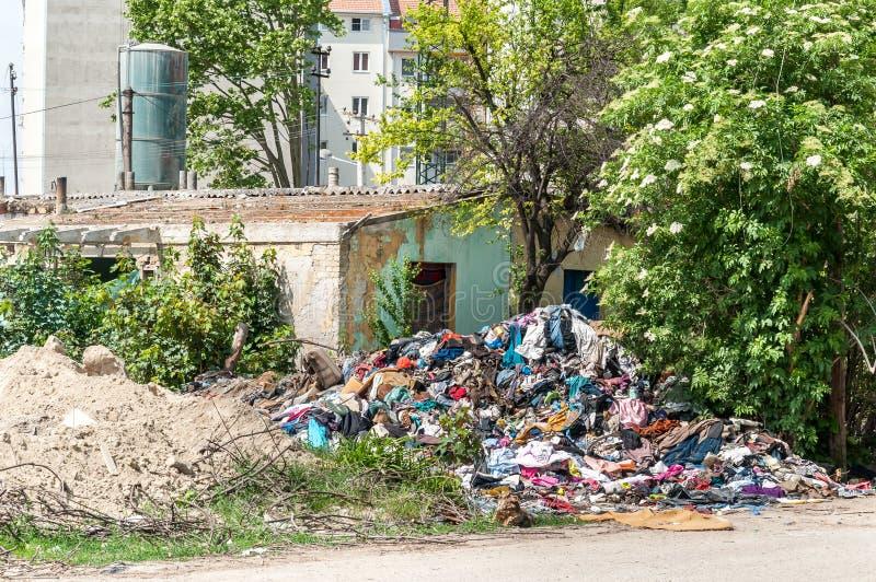 Övergett lantligt skadat hus i gettot nära ny bostads- byggnad i staden som används som avskrädeförrådsplats med skräp och kull i royaltyfri foto