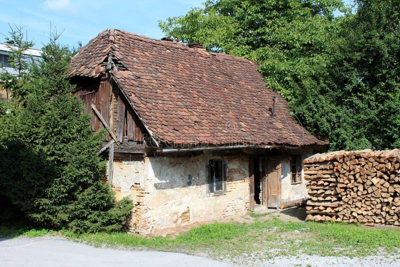 Övergett litet familjhus med spruckna väggar och förfallna fasaden som täckas med missande delvist taktegelplattor som omges med arkivfoton