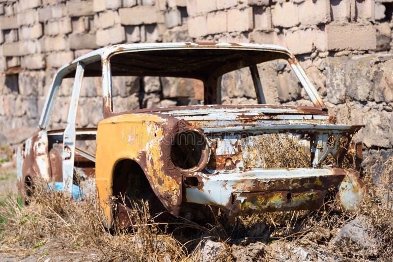 Övergett och rostigt skelett av en sovjetisk rysk bil vid sidan av byggnadsyttersidan arkivfoton