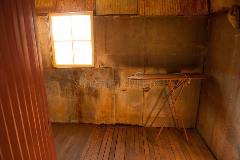 Övergett rum med strykbrädet i gammalt hus fotografering för bildbyråer