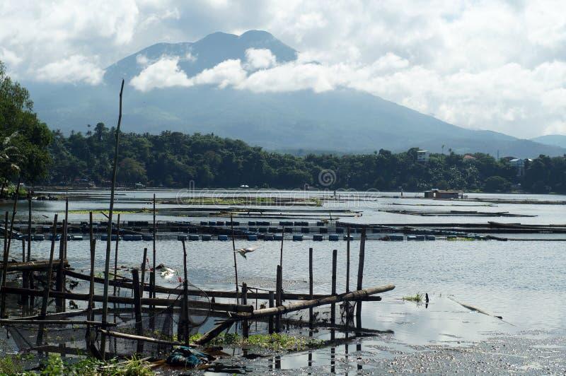 Övergett ruttna bambufiskburar längs bergsjön royaltyfri fotografi