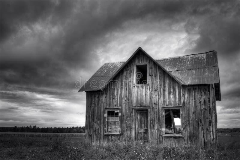 Övergett spökat lantgårdhus med stormig himmel royaltyfri fotografi