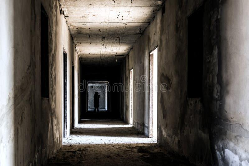 Övergett ställe för byggnadsspökeuppehälle med den läskiga kvinnan inom arkivfoto
