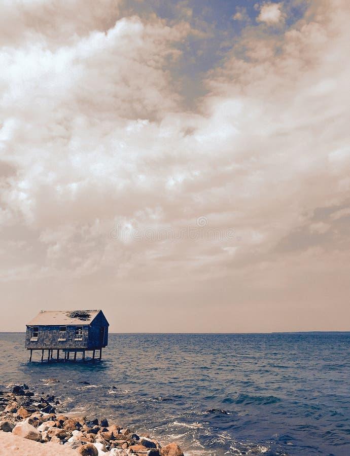 Övergett styltahem i havet royaltyfri foto