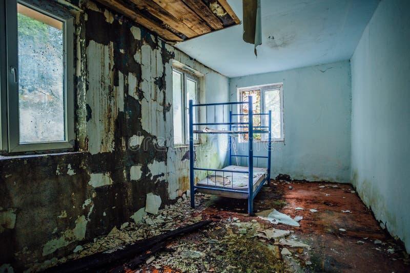 Övergett vandrarhem Kusligt smutsigt och övergett sovrum med sprucken väggar och dubbeldäckaresäng arkivbilder