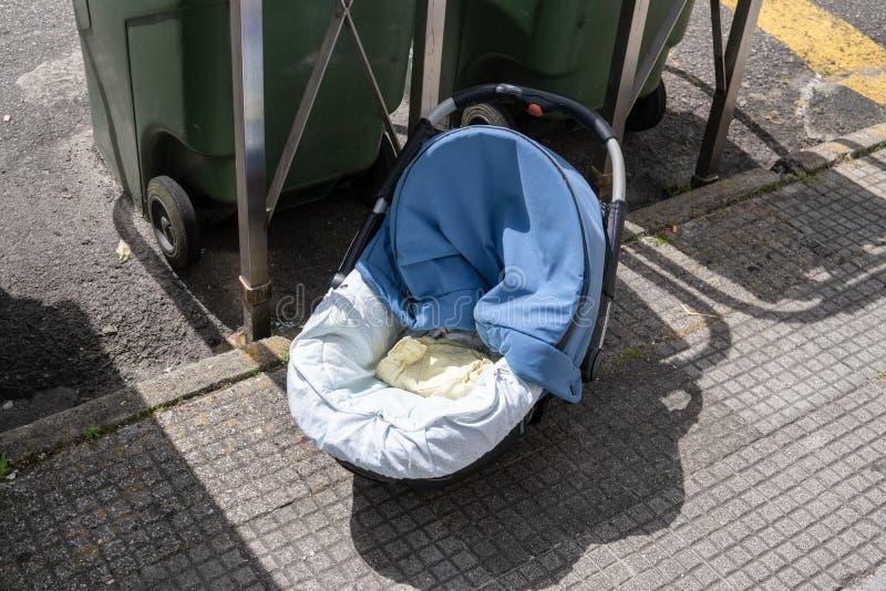 Övergiven barnvagn nära offentligt avfallfack på trottoaren royaltyfria foton