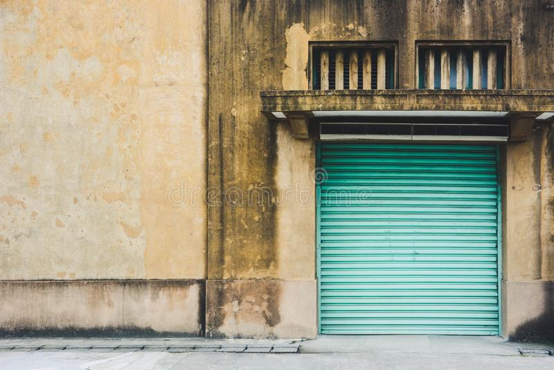 ?vergiven fabriksbyggnad, gammal gul byggnad f?r lagringslager med den st?ngda gr?na d?rren f?r metallrullslutare arkivbilder