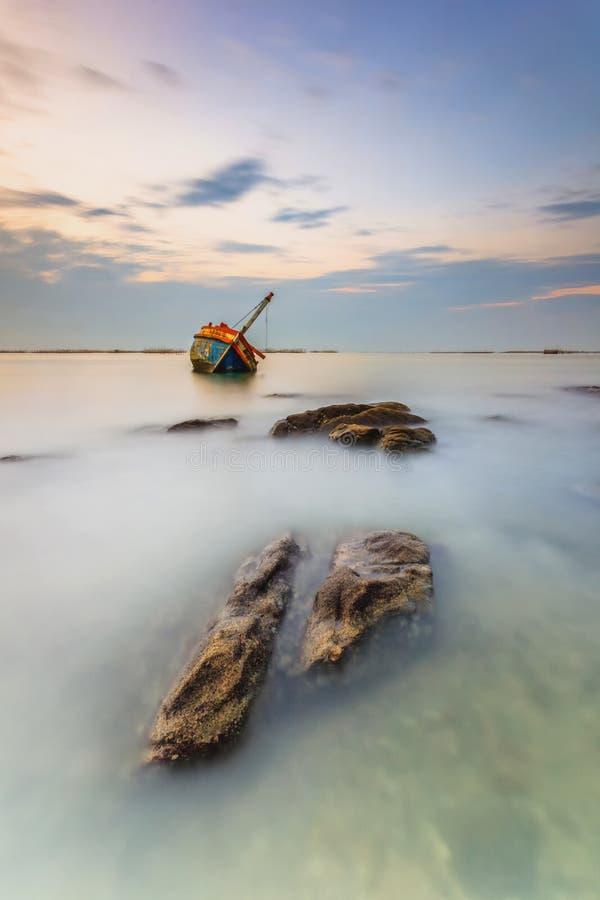 Övergiven fiskebåt med härlig solnedgång på havet arkivbild
