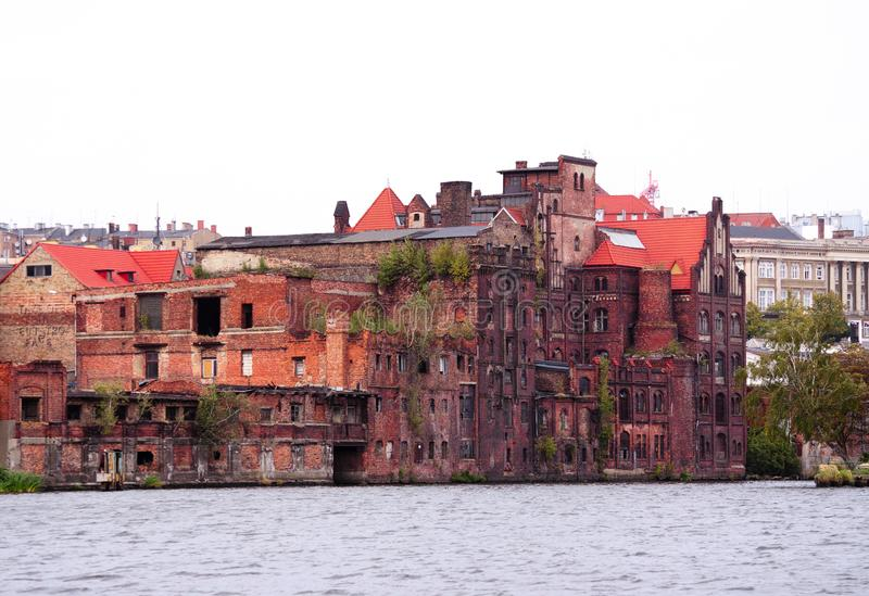 Övergiven gammal fabrik på flodbanken - gammal arkitektur av staden - Szczecin Polen royaltyfri fotografi