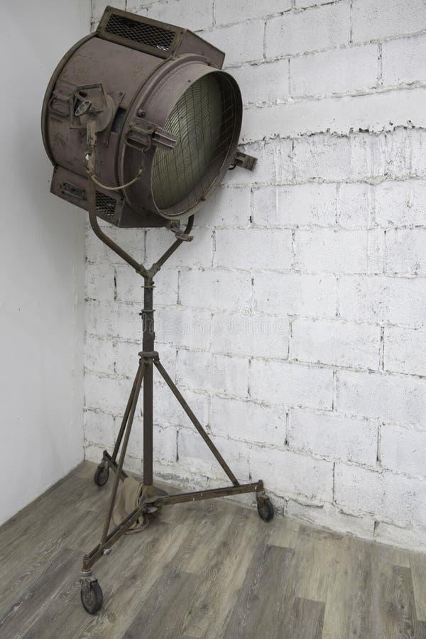 Övergiven gammal lantlig metallstrålkastare med ställningen arkivbild
