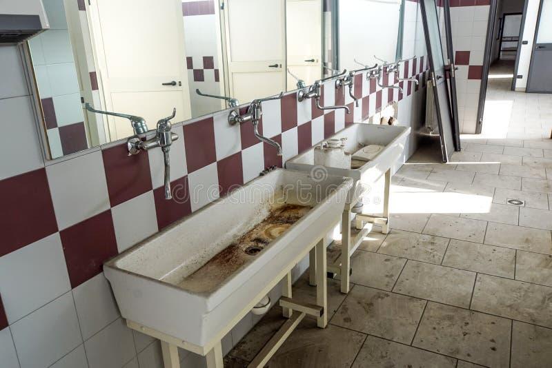 Övergiven gammal toalett i förstörd byggnad, inre industriell lantgård royaltyfri fotografi