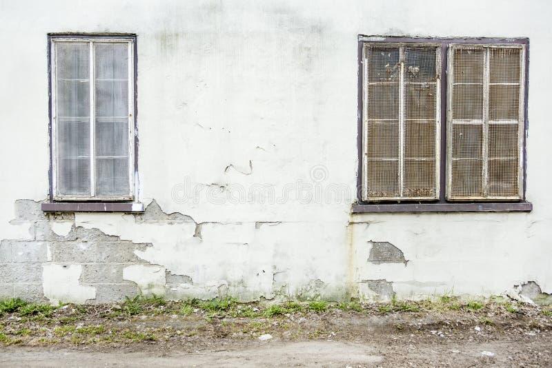 Övergiven grunge knäckte tegelstenstuckaturväggen med skyddsgallrar för ett fönster fotografering för bildbyråer