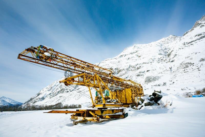 Övergiven konstruktion för gul metall eller konstruktionsutrustning på bakgrunden av snöig berg och blå himmel royaltyfri foto