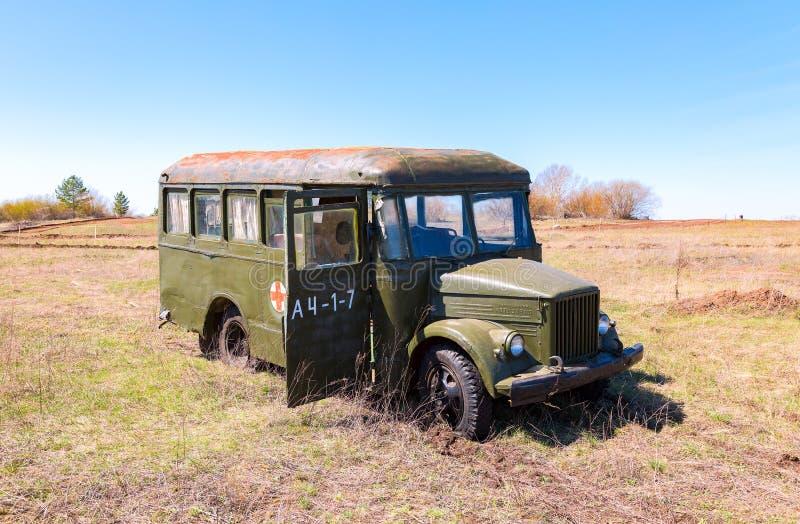 Övergiven retro buss för armé gräsplan i natur royaltyfri bild