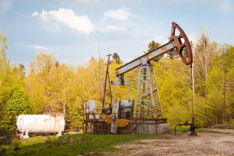 Övergiven rostig bruten oljapump och rörledningutrustning i skogen, oljaextraktionrigg, vårafton royaltyfri fotografi