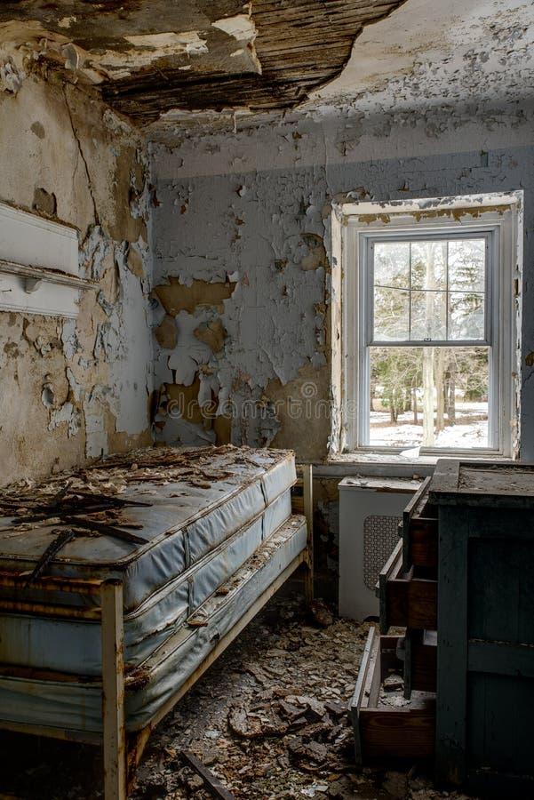 Övergiven säng i sovrummet - övergiven Sleighton lantgårdskola - Pennsylvania arkivbild