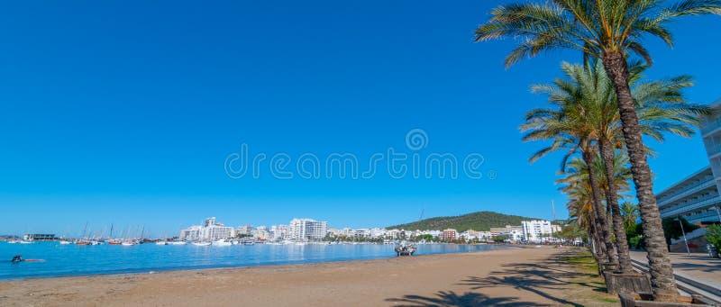 Övergiven segelbåt på Ibiza strand Mannen paddlar hans bräde in mot en övergiven segelbåt Balearic Island Spanien arkivbilder