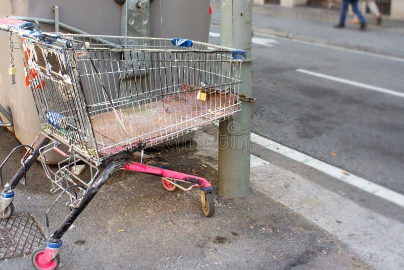 Övergiven shoppa vagn av en hemlös som kedjas fast till lyktstolpen med hänglåset Målat i rosa färger royaltyfri foto