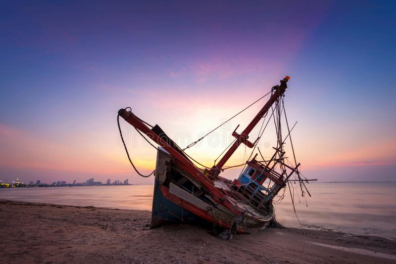 Övergiven skeppsbrott av den wood fiskebåten på stranden på skymningsi royaltyfri bild