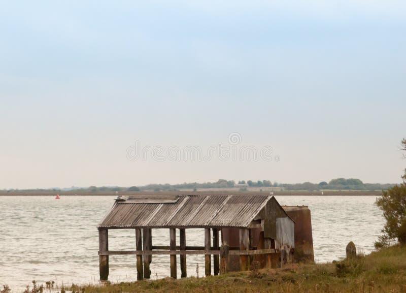 Övergiven skjulhydda på kanten av kustvattenhavet royaltyfri foto