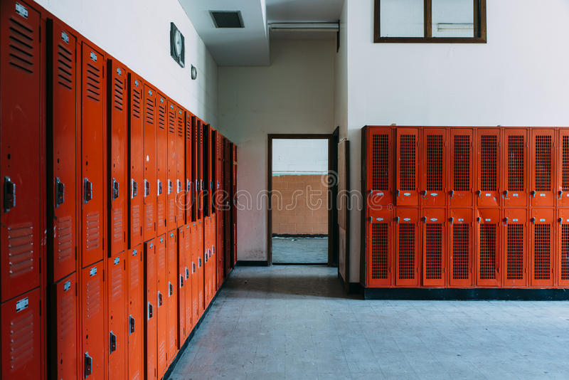 Övergiven skolaomklädningsrum med låsbara skåp med orange skåp royaltyfria bilder