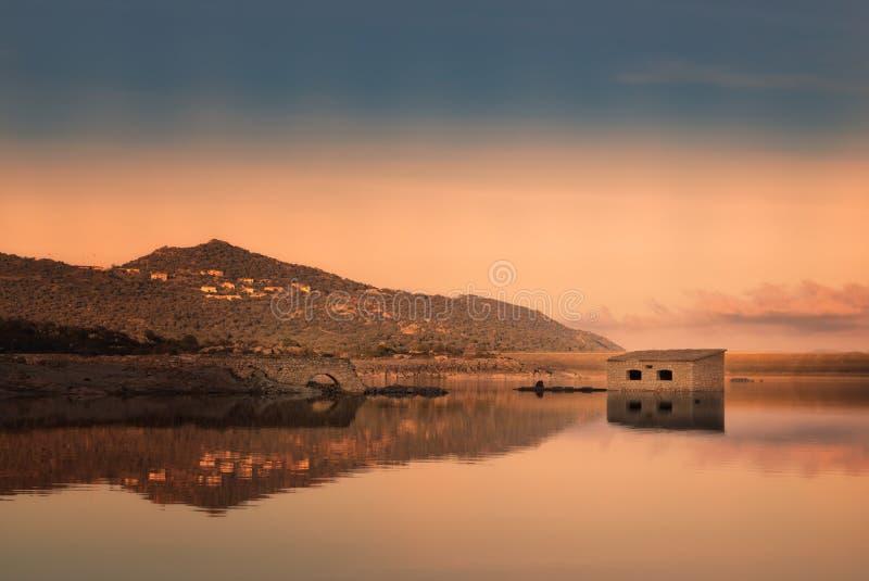 Övergiven stenbyggnad reflekterade i sjön på solnedgången royaltyfri bild