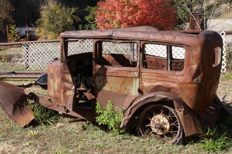 Övergiven tappningbil i spökstad royaltyfri fotografi