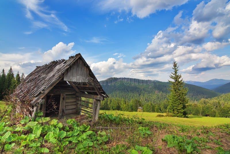 Övergiven träladugård i bergen och skogen. royaltyfri fotografi