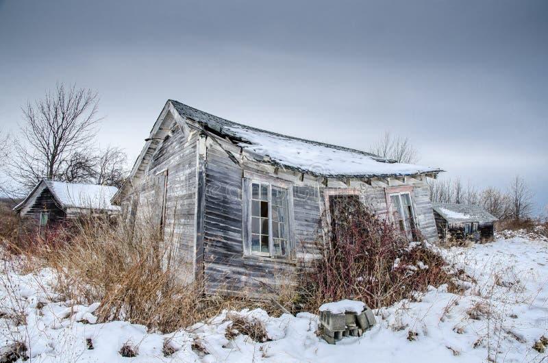 Övergiven turist- kabin i fält med snö fotografering för bildbyråer