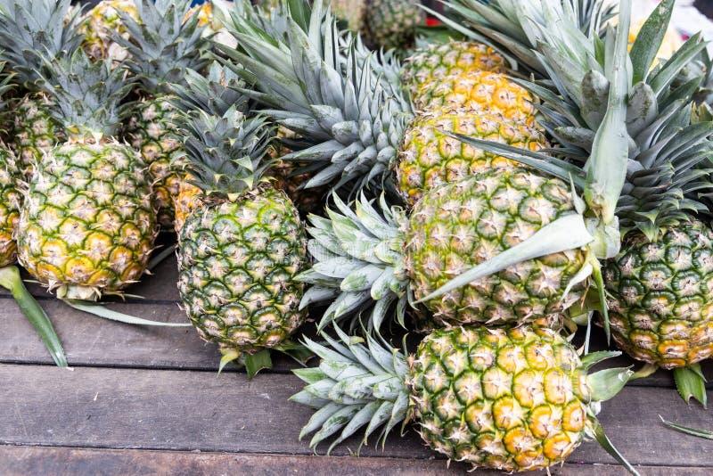 Överhopa av nytt skördad organisk ananas på träyttersida royaltyfri fotografi