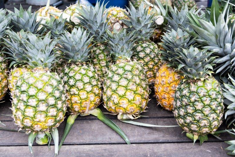 Överhopa av nytt skördad organisk ananas på träyttersida arkivfoto