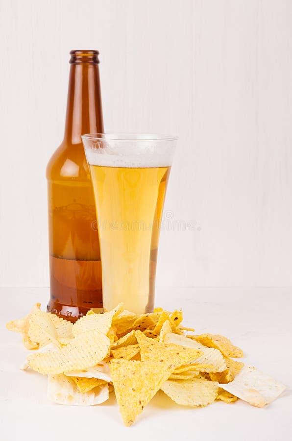 Överhopa olikt frasigt guld- mellanmål och öl i exponeringsglas, brun flaska på mjuk vit wood bakgrund royaltyfri foto