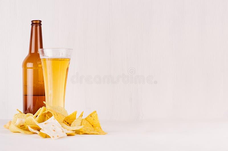 Överhopa olikt frasigt guld- mellanmål och öl i exponeringsglas, bruntflaska på mjuk vit wood bakgrund, med kopieringsutrymme royaltyfria bilder