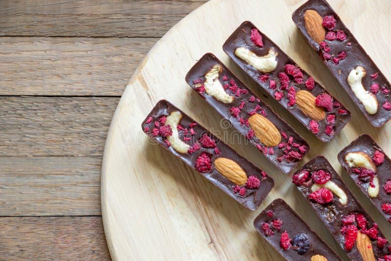 Överkänslig syn på utsökta råa livsmedel som framställs av naturlig choklad, cashew, mandel och hallon Söta pinnar läggs runt fotografering för bildbyråer