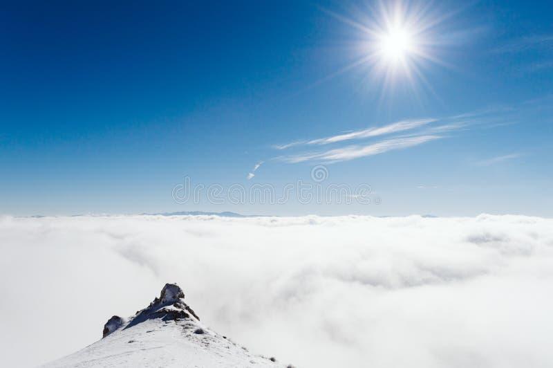 Överkant av berget som täckas med snö, dimma, is och den förbluffahimmel och solen royaltyfri foto