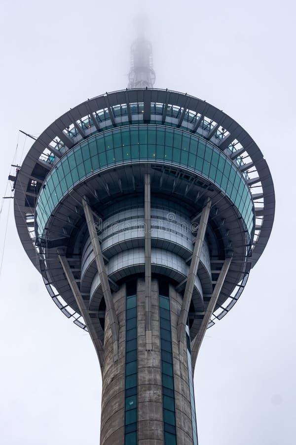 Överkant av det Macao tornet som försvinner i moln royaltyfri fotografi