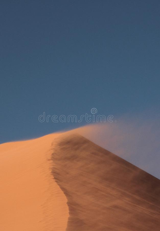 Överkant av dyn 45 som vinden lyfter i sanden arkivfoton